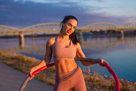 Young athlete woman holding hoop at riverbank during sunrise