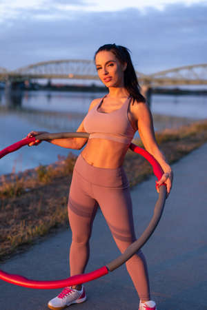 Young sporty woman holding hoop at riverbank during sunset 版權商用圖片