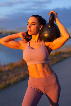 Young woman holding kettlebell on shoulder at riverbank in golden sunset 版權商用圖片