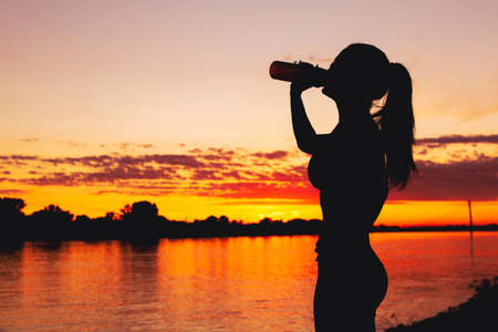 Thirsty young woman silhouette drinking refreshment from bottle at riverbank in sunset 版權商用圖片