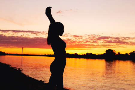 Sexy young woman silhouette with arms up at riverbank sunset during golden hour