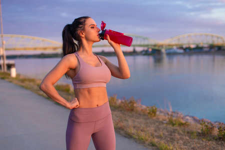 Thirsty young woman in sportswear drinking refreshment from bottle at riverbank