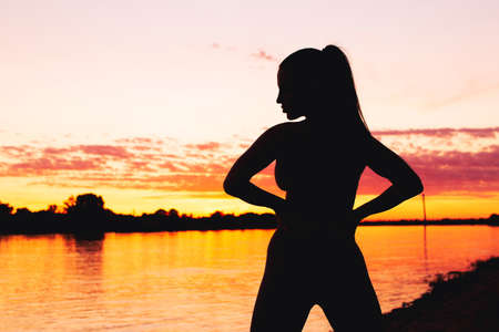Sexy young woman silhouette in golden sunset at riverbank horizontal