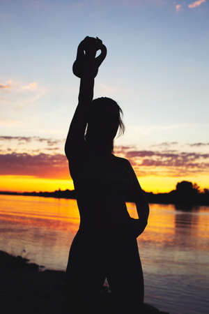 Young sporty woman silhouette holding kettlebell at riverbank