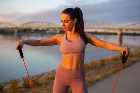 Young woman doing biceps exercise by expander at riverbank, horizontal