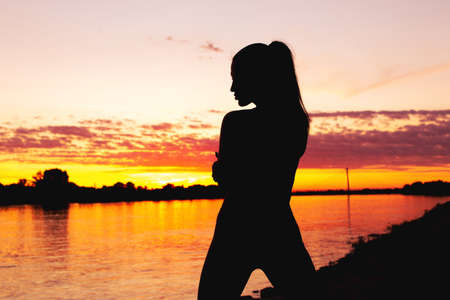 Sexy young woman silhouette in sunset at riverbank horizontal 版權商用圖片