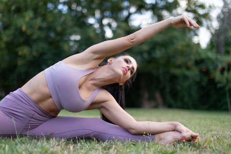 Young sportswoman doing stretching exercise in garden on grass, outdoors