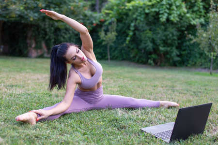 Young woman in sportswear learning from tutorial video stretching in garden, outdoors 版權商用圖片