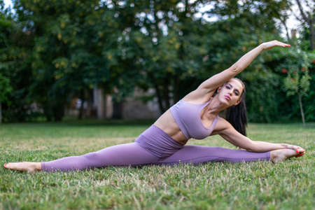 Young woman in sportswear stretching in split pose at garden on grass, outdoors 版權商用圖片
