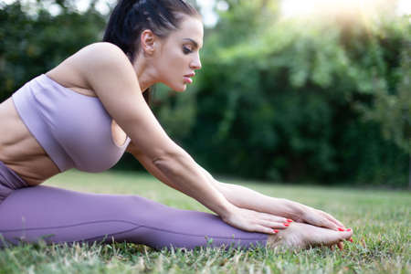 Young woman in sportswear stretching in garden on grass, outdoors, in sunset