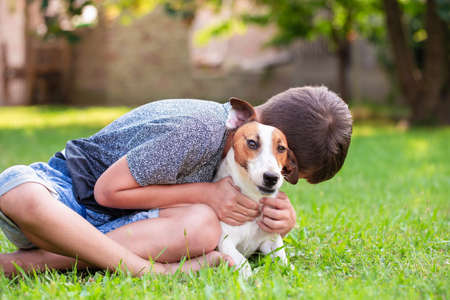 Little boy embracing Jack Russell Terrier in grass, dog therapy