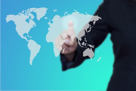 Businessman pushing a button on a world map. photo