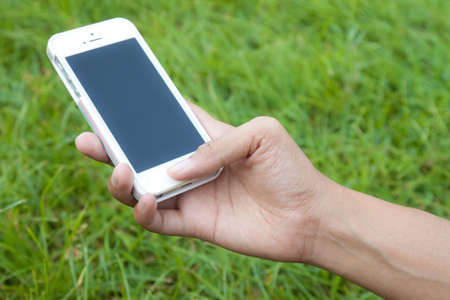 Woman hand holding smartphone in park photo