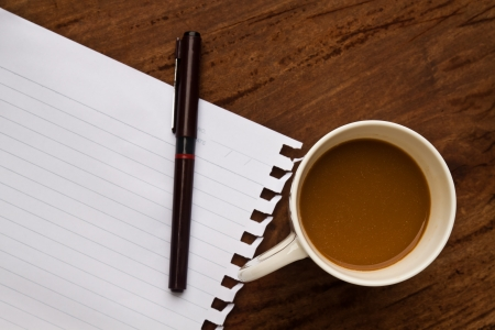 coffee with note and pen  on old  wood background photo