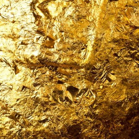 Gold leaf on buddha sculpture background.