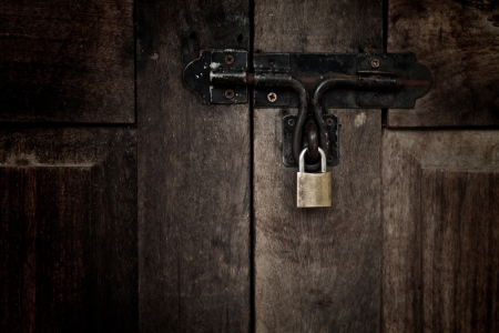 Old padlock on wooden door photo