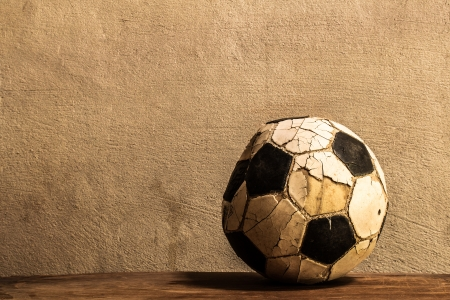 Old football on concrete background
