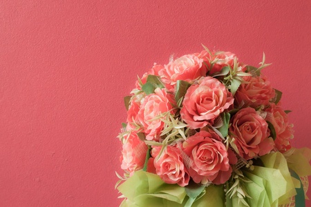 Rose, artificial flowers and red wall background. photo