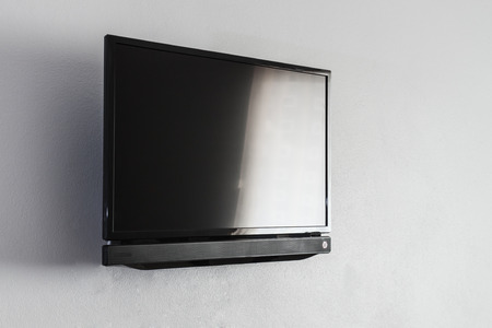 Black LCD of LED-tv-scherm opknoping op een muur achtergrond