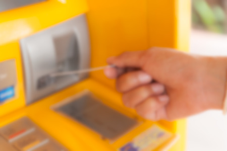 withdraw: out of focus hand inserting ATM credit card into bank machine to withdraw money