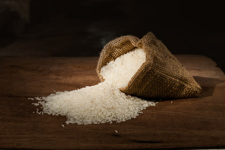 rice in small burlap sack on wooden table photo
