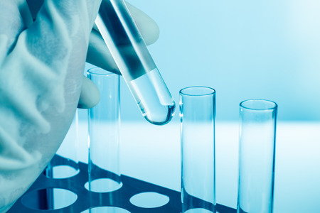 Scientist hand holding a test tube in the laboratory photo