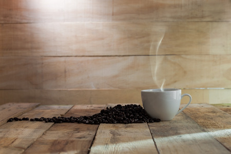 cup of black coffee and beans over wood background photo