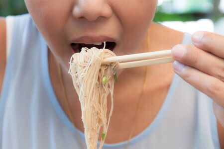 eating noodles: Asian woman eating noodles