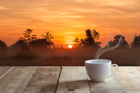 cup of black coffee over wood table and Sunset
