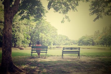 빈티지 스타일의 공원에서 벤치에 아시아 젊은 외로운 여자,