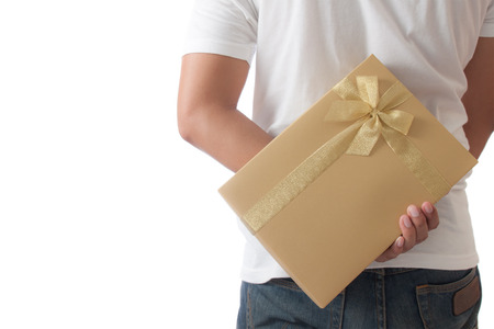 gift behind back: Man hiding a golden gift box giving for surprise Stock Photo