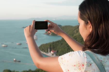 mujer mirando el horizonte: mujer asiática con teléfono inteligente tomar una foto en la isla de Koh Larn en Pattaya, Tailandia