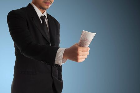 giving money: Business man giving money  on blue background Stock Photo