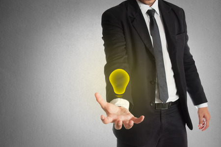 bright light: Businessman is holding a lightbulb , The concept of Business creative