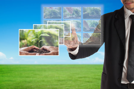 Business concept of  CSR or Corporate Social Responsibility,businessman select a photo on touch screen for plan csr