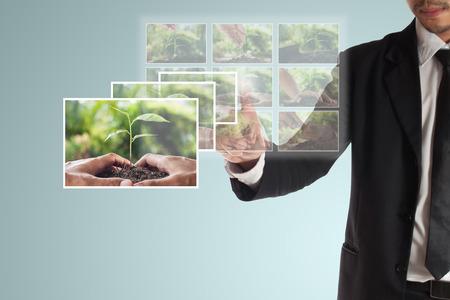CSR や企業の社会的責任のビジネス ・ コンセプト ビジネスマンは、プラン csr のタッチ ・ スクリーンで写真を選択します。