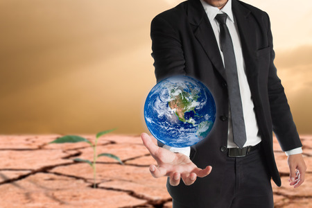 conservationist: Businessman holds Earth in a hand , global warming concept. Elements of this image are furnished by NASA