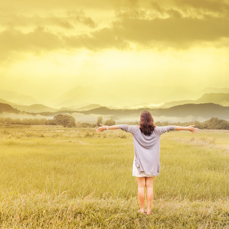 beatitude: asian woman with arms outstretched in a  field Stock Photo