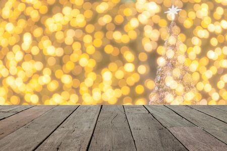 christmas lights display: wood table in front of golden  christmas bokeh lights, empty wood table for product display Stock Photo