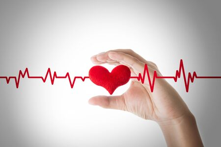 hands holding red heart with ecg line on white background, Heart or pulse rate concept. Archivio Fotografico