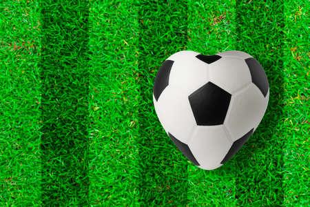 heart symbol: Heart shaped soccer ball on green grass
