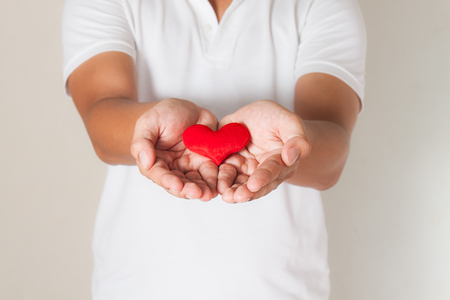 red heart in asian man hands,health- medicine and charity concept Stock Photo
