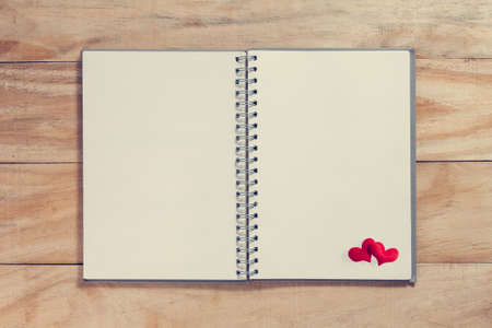 heart shaped stuff: notebook with red heart on wood table ,Valentines background in vintage style