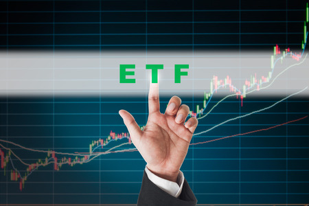 traded: businessman touching ETF (Exchange Traded Funds)  text on  touch screen interface with stock graph background