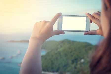 mujer mirando el horizonte: asian woman using smart phone take a photo at koh larn island  in Pattaya ,Thailand Foto de archivo