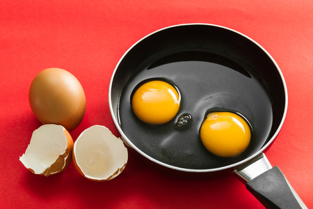 raw egg in pan on red  background Stock Photo