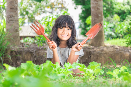 Young girl holding gardening shovel and fork  in vegetable bed