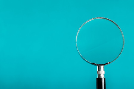 Magnifying glass on blue color background. Stock Photo