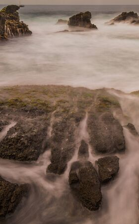Beautiful waves in a rocky beach in Sawarna Beach at dusk, I enjoy it while waiting for sunset