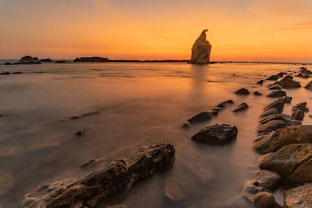Wonderful seascape in Sawarna Beach, enjoying the golden sunset and rocky beach view at dusk accompanied  a cup  tea